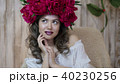Girl model posing. a young woman in a wreath of scarlet peonies on her head, dark long curly hair 40230256