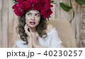 Girl model posing. a young woman in a wreath of scarlet peonies on her head, dark long curly hair 40230257