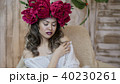 Girl model posing. a young woman in a wreath of scarlet peonies on her head, dark long curly hair 40230261