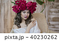 Girl model posing. a young woman in a wreath of scarlet peonies on her head, dark long curly hair 40230262