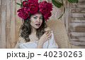 Girl model posing. a young woman in a wreath of scarlet peonies on her head, dark long curly hair 40230263