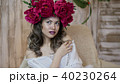 Girl model posing. a young woman in a wreath of scarlet peonies on her head, dark long curly hair 40230264