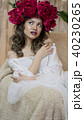 Girl model posing. a young woman in a wreath of scarlet peonies on her head, dark long curly hair 40230265