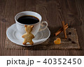 a cup of coffee and cookies like bear and heart with cinnamon, coffee beans on wooden table 40352450