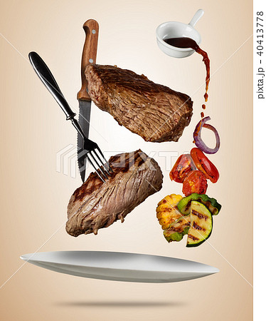 Flying beef steaks with grilled vegetable served on plate. 40413778
