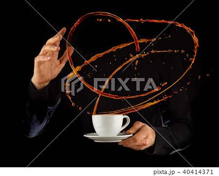 Man hands holding porcelaine cup with splashing liquid of coffee or tea, isolated on black backround 40414371