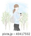 コーヒーを持って歩く女性 40417502