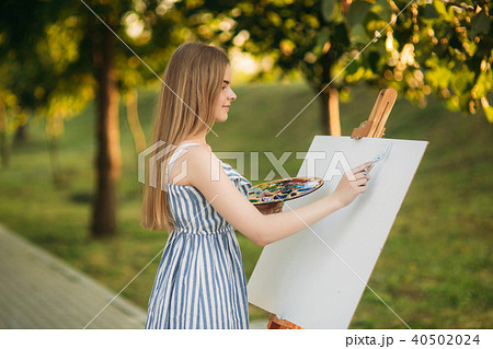 Beautiful girl standing in the park and draws a picture using a palette with paints and a spatula. 40502024