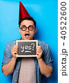 Young man in birthday hat with blackboard 40522600