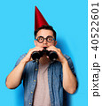 Young man in birthday hat with binoculars 40522601