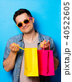 Young man in sunglasses holding a shopping bags 40522605