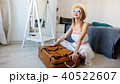 girl and classic siutcase sitting on a floor 40522607