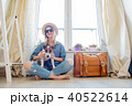 Young girl with dog sitting next to suitcase 40522614