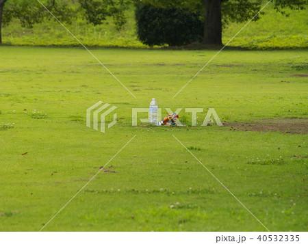 公園の芝生に置かれたペットボトルとタオル 40532335