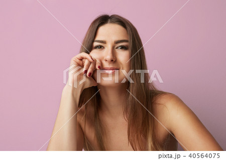 Fashion portrait of a beautiful smiling woman with long hair over empty pink background. Fashion 40564075