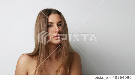 Young beautiful woman posing at the camera impressively on a light Background. Pensive Beauty Woman 40564096