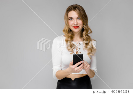Attractive young blonde business woman in black and white clothes smiling holding mobile phone in 40564133