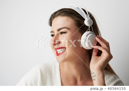 Smiling beautiful young woman listening to music on headphones over empty light background at studio 40564150