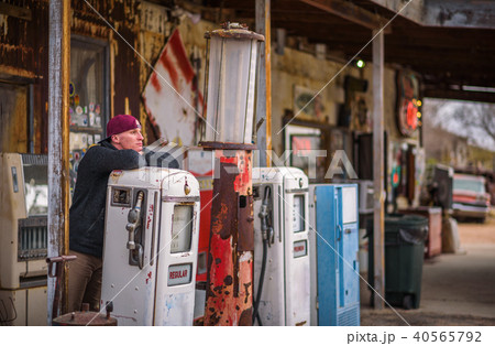 Young man at a vintage gas pump 40565792