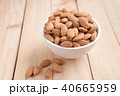 Almond nut in a ceramic bowl against wooden table 40665959