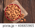Almond nut in a ceramic bowl against wooden table 40665965