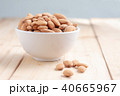 Almond nut in a ceramic bowl against wooden table 40665967