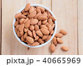 Almond nut in a ceramic bowl against wooden table 40665969
