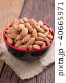 Almond nut in a ceramic bowl against wooden table 40665971