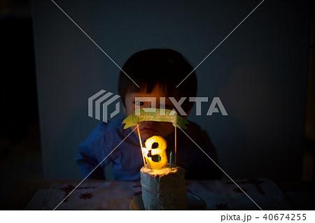 子供の三歳の誕生日/バースデーケーキのロウソクを吹き消す 40674255