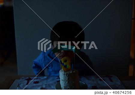 子供の三歳の誕生日/バースデーケーキのロウソクを吹き消す 40674256