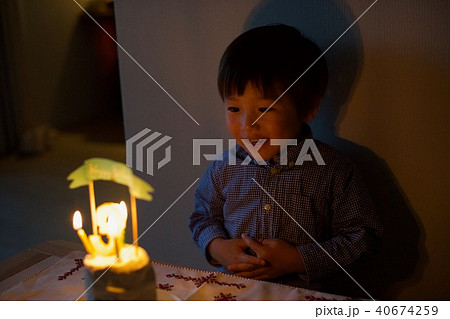 子供の三歳の誕生日/バースデーケーキのロウソクを吹き消す 40674259