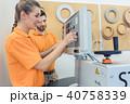 Team of carpenters programming CNC machine in their workshop  40758339