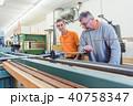 Senior carpenter and female apprentice working on band grinder 40758347