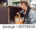 Woman carpenter loading tools in mobile workshop transporter 40758348