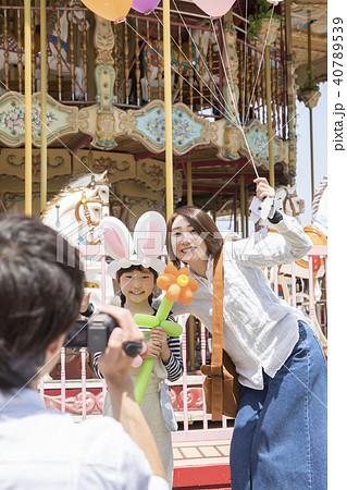 遊園地でお母さんと娘を撮影するお父さん 40789539