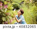 携帯で庭の花を撮る女性 40832065