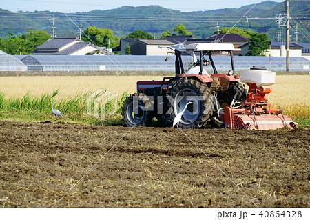 田を耕すトラクターの横で獲物を探す鷺(サギ) 40864328
