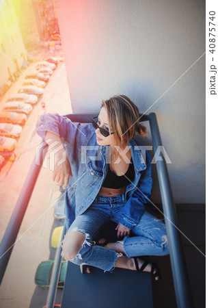 girl in jeans clothes and sunglasses on balcony 40875740