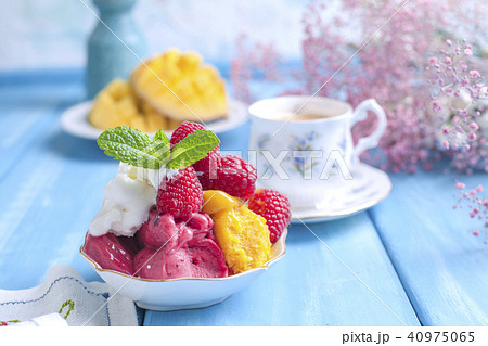 Ice cream of bright colors with mango, raspberry and mint in a plate, on a blue wooden background. A 40975065