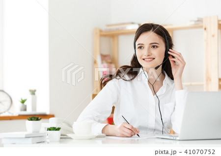 Call Center Concept: Portrait of happy smiling female customer support phone operator at workplace. 41070752