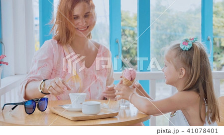 Young mother and her little daughter spending time in a cafe with ice cream 41078401