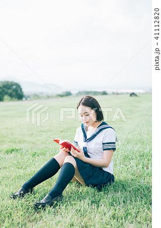 芝生に座って本を読む高校生 41112820