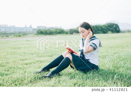 芝生に座って本を読む高校生 41112821