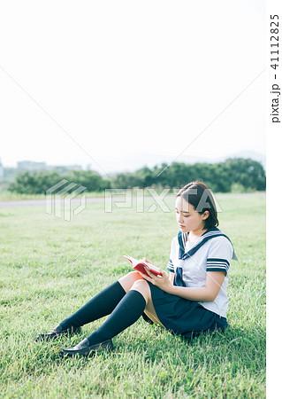 芝生に座って本を読む高校生 41112825