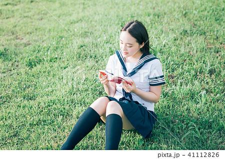 芝生に座って本を読む高校生 41112826