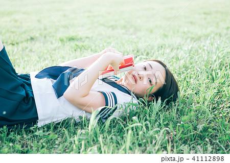 芝生に寝転がって本を読む高校生 41112898