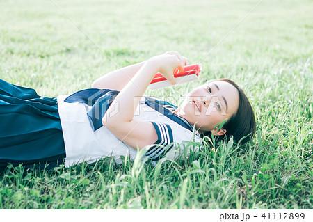 芝生に寝転がって本を読む高校生 41112899