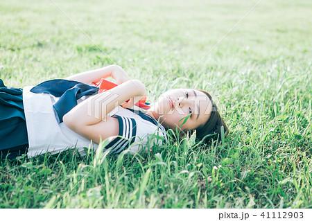 芝生に寝転がって本を読む高校生 41112903