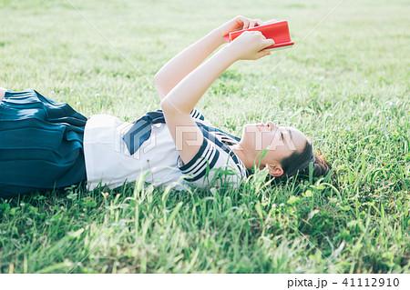 芝生に寝転がって本を読む高校生 41112910