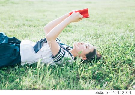 芝生に寝転がって本を読む高校生 41112911